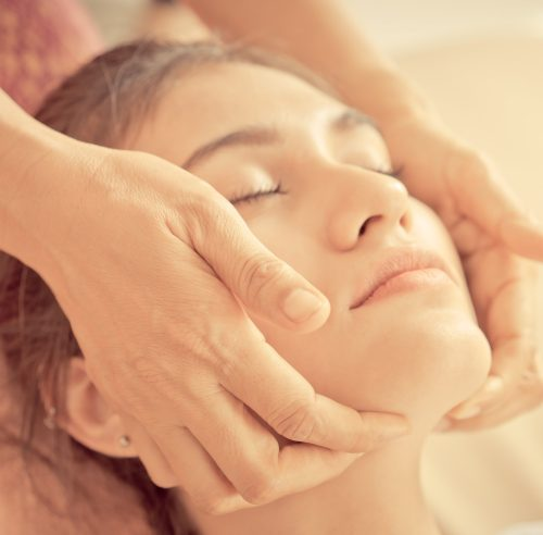 Therapist hand is massaging on a woman face in spa
